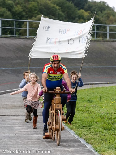 Former Belgian champion Eddy Planckaert is followed by childrens with a banner during his attempt to set a new world hour record on a wooden bike at the velodrome in Rochefort, Belgium on September 25, 2015.